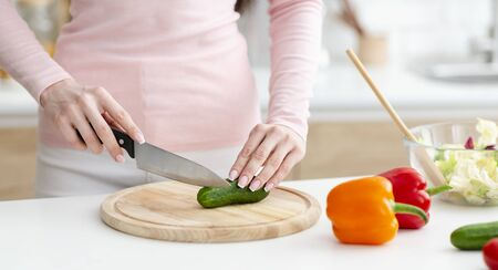 Cooking at home. Woman cutting fresh vegetables for salad on wooden board, panorama