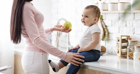 Tooth strengthening. Mom giving fresh apple to little baby son, sitting on kitchentop, panorama