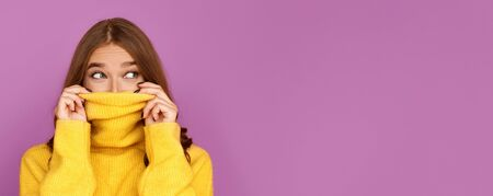 Girl pulling her trendy sweater over head, having fun and looking at free space on purple background