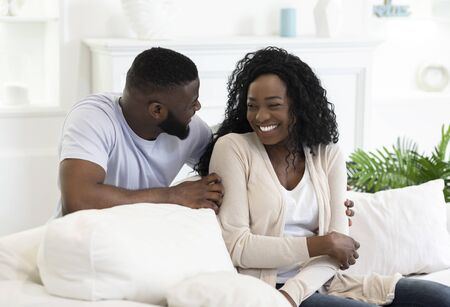 Cheerful african american couple having fun at home, enjoying weekend together. Copy space