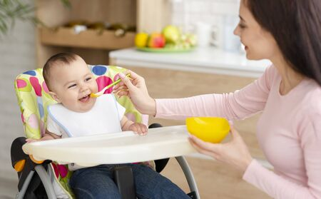 Baby nutrition. Young woman feeding her cute toddler in kitchen