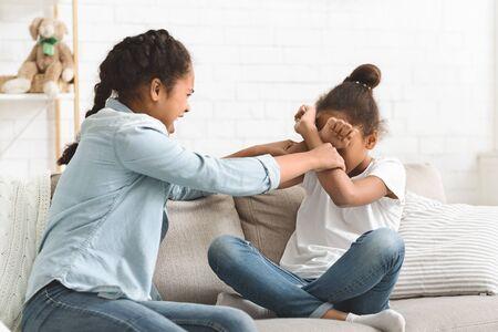 Two teenaged african girls fighting at living room, sisterhood conflict, copy space 写真素材