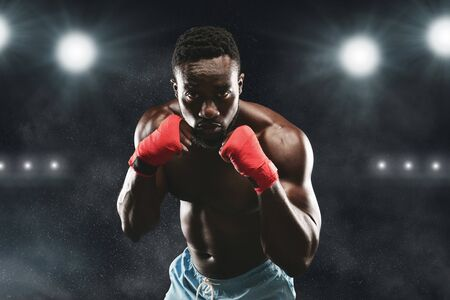 Young african fighter in boxing stance standing on fighting ring, stadium lights background