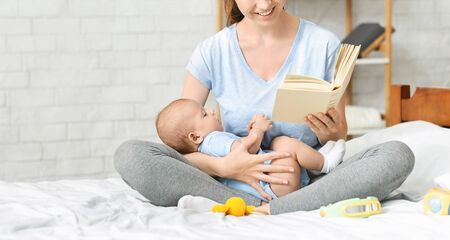 Happy mother reading book to her toddler at home, panorama with copy space