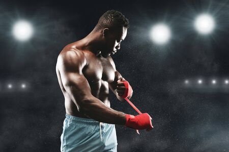 Professional african american boxer wrapping his fists before fight over stadium background, free space 版權商用圖片