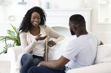 Conversación agradable. Joven esposo y esposa charlando juntos en la sala de estar en casa.