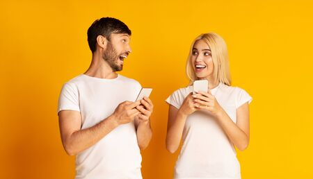 Face-To-Face Conversation. Excited Man And Woman Talking Holding Smartphones Looking At Each Other Standing Over Yellow Background. 写真素材