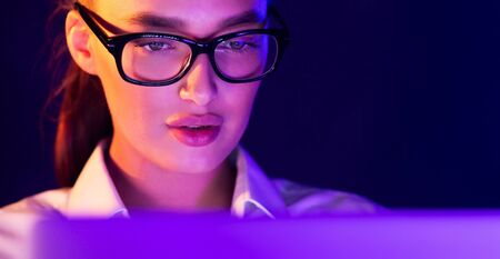 Young woman working on laptop late at night, face illuminated by neon light, free space Stok Fotoğraf