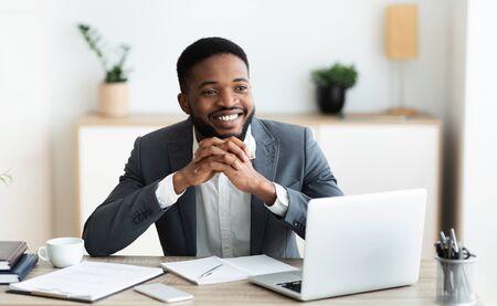 Soñador. Ceo afroamericano pensativo pensando en el futuro brillante de su empresa, panorama Foto de archivo