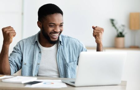 Great news. Euphoric african american entrepreneur celebrating business success with raised arms, looking at laptop screen with excitement