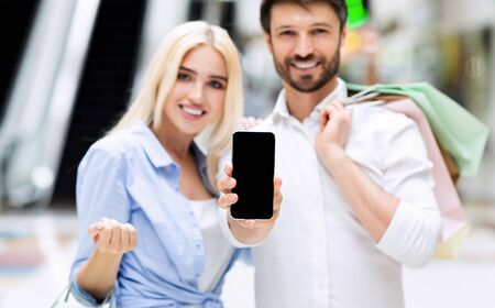 Shopping Application. Cheerful Spouses Showing Empty Mobile Phone Screen To Camera Standing In Mall Center. Shallow Depth, Mockup 写真素材