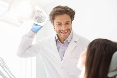 Cheerful handsome dentist greeting his female patient at dental office, empty space Stockfoto