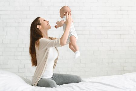 Young mother playing with her infant son lifting him up in the air in bedroom, copy space