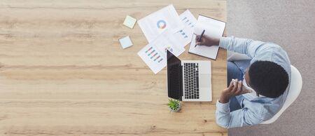 Draufsicht des Büroarbeitsplatzes. Beschäftigter Geschäftsmann, der am Holzschreibtisch mit Laptop arbeitet, telefoniert und Notizen macht, Panorama mit Kopierraum Standard-Bild