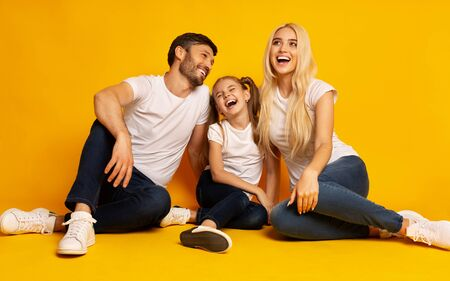Family Happiness. Parents And Daughter Laughing Sitting Together On Floor Having Fun In Studio Over Yellow Background. Фото со стока