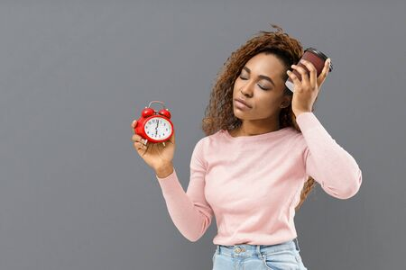 Morning coffee. Mixed race sleepy girl with closed eyes holding red alarm clock and cup of coffee, grey background, copy space Banco de Imagens
