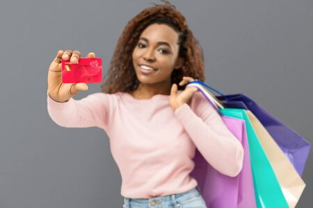 Happy young mixed race woman recommending credit card, posing with shopping bags and looking at camera, grey background