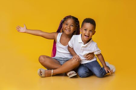 Cute little black girl cuddling her adorable baby brother, sitting on floor, looking aside and gesturing over yellow background, copy space Stok Fotoğraf