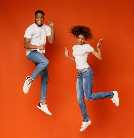 Couple fun. Cheerful african guy and girl jumping in air, orange studio background Banco de Imagens