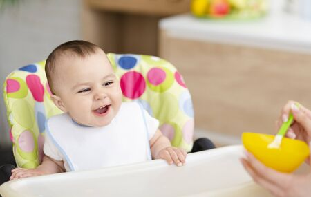 Favorite meal. Adorable baby enjoying porridge, sitting in high chair at kitchen, free space Stock Photo