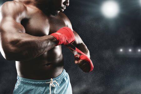 Luchador afro envolviendo sus puños, permaneciendo en el ring de boxeo, espacio de copia
