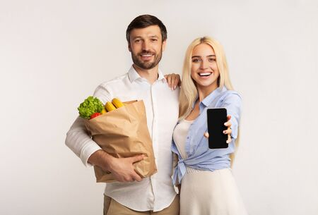 Couple Showing Empty Cellphone Screen Holding Grocery Shopping Bag Embracing On White Background. Studio Shot, Mockup