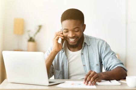 Geweldig nieuws. Portret van een vrolijke Afro-Amerikaanse zakenman die aan de telefoon praat en documentatie leest op de werkplek