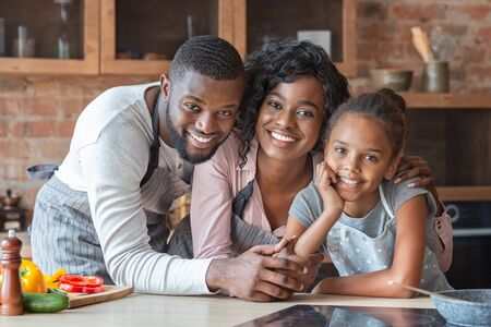 Cheerful black family spending time together at kitchen, looking at camera and smiling