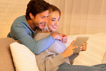 Evening Together. Loving Couple Watching Film On Tablet Computer Sitting On Sofa Indoor. Selective Focus Stok Fotoğraf