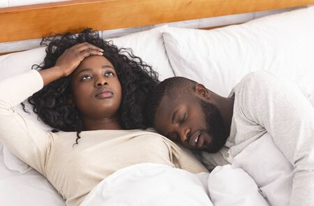 Frustrated young woman annoyed by her husband snoring loudly in bed, can not sleep and touching her head in despair.