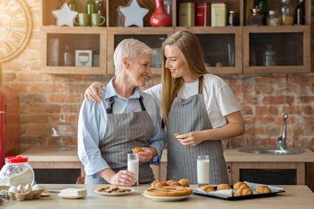 Baking with my mom is very inspiring. Adult daughter baking with aged mother, having snack, drinking milk, copy space Stok Fotoğraf
