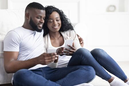 Black millennial couple using smartphone together checking social networks, sitting on sofa at home 写真素材