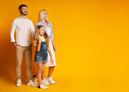 Family Of Three Smiling Looking At Copy Space Standing On Yellow Background. Studio Shot
