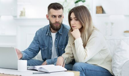 Worried family managing finances, using laptop computer at home