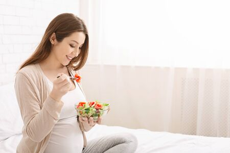 Healthy organic nutrition. Pregnant millennial woman eating natural vegetable salad in bed, empty space Stock Photo