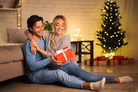 Presents time. Man giving new year present to wife, sitting on floor and enjoying holidays together
