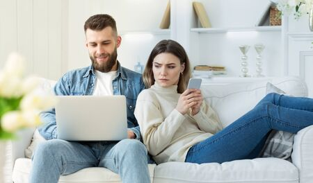 Distrust in relationships. Wife spying at mans laptop, sitting on sofa with cellphone in hands Stockfoto - 132080435