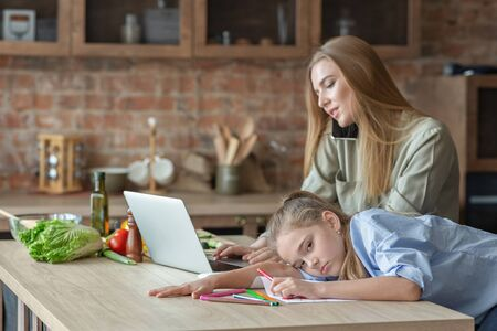 Blondy daughter feeling bored, mother talking by phone and looking at laptop, kitchen interior, copy space Stockfoto