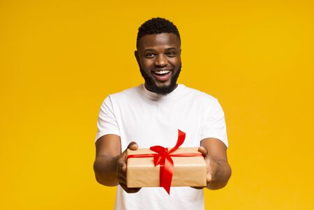 Theme holidays. Cheerful african american man offering exclusive gift box wrapped with red ribbon and bow to camera Foto de archivo