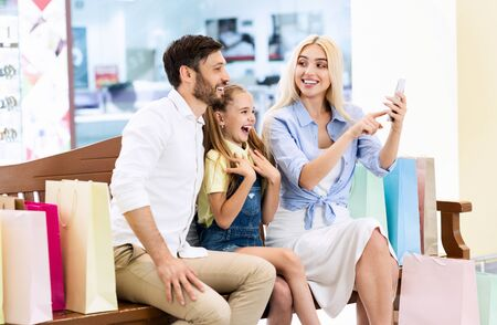 Shopping App. Family Using Mobile Phone Application Searching Discounts And Sales Sitting On Bench In Mall. Foto de archivo - 132080506