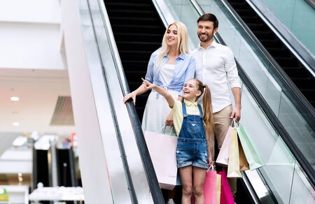 Family Shopping Concept. Daughter Pointing Finger Standing On Escalator Asking Parents To Buy Something In Mall. Free Space