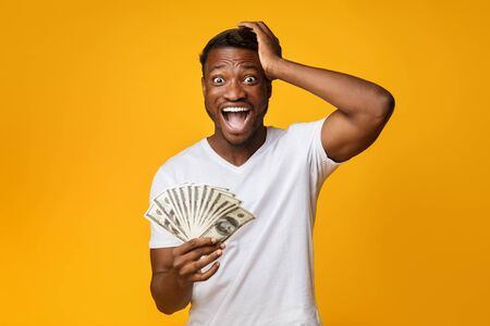 Excited Afro Guy Holding Money Shouting Touching Head Standing On Yellow Studio Background. Big Luck. Free Space 写真素材