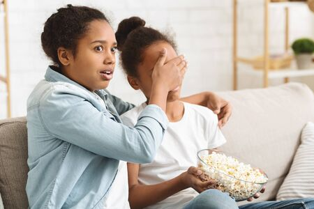 Scary moment in horror movie. Little african sisters watching TV at home, older girl closing her little sister eyes, copy space