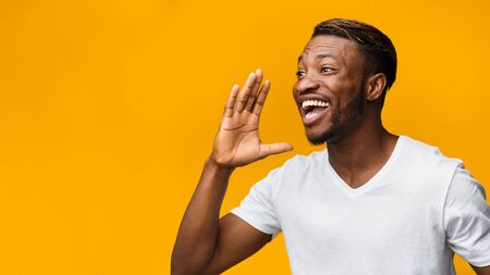 Attention. Funny African American Man Shouting Holding Hand Near Mouth On Yellow Studio Background. Panorama, Copy Space