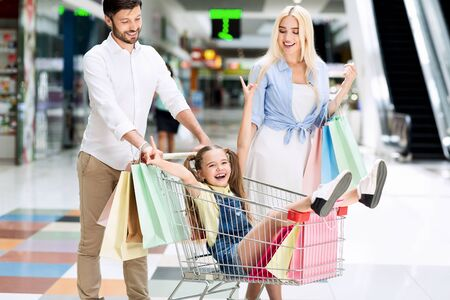 Parents Riding Excited Little Daughter In Shopping Cart Walking Spending Time In Mall Center. Banco de Imagens