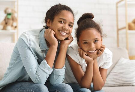 Adorable african sisters having fun together at home, sitting on sofa and smiling at camera, copy space