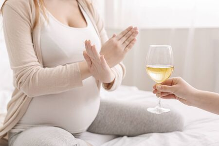 Alcohol prohibited. Pregnant woman with crossed hands refusing to drink wine, making denying gesture to glass, copy space