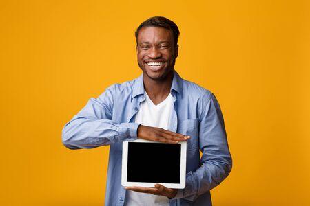 Great App. Smiling African American Man Showing Empty Tablet Screen On Yellow Background In Studio. Mockup Reklamní fotografie