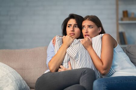 Two Scared Girls Hugging Pillows Sitting On Couch Alone At Home While Somebody Trying Break Into House. Free Space Stok Fotoğraf