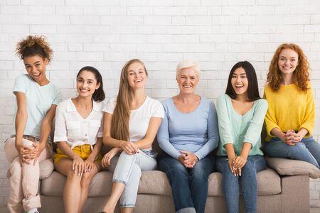 Lächelnde verschiedene Frauen, die die Kamera betrachten, die auf dem Sofa über der weißen Mauer im Innenbereich sitzt. Zusammengehörigkeitskonzept